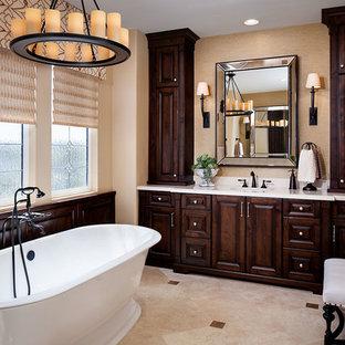 Ispirazione per una stanza da bagno padronale classica di medie dimensioni con ante in legno bruno, vasca freestanding, pavimento in travertino, ante con bugna sagomata, lavabo sottopiano e pareti beige