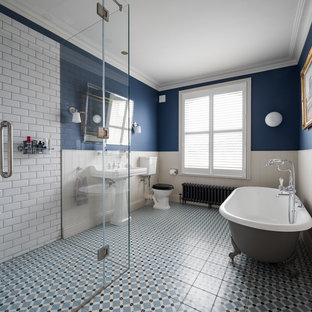 Design ideas for a classic ensuite bathroom in London with a claw-foot bath, a corner shower, a two-piece toilet, white tiles, metro tiles, multi-coloured walls, a pedestal sink, blue floors and a hinged door.