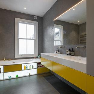 Modelo de cuarto de baño moderno, de tamaño medio, con armarios con paneles lisos, puertas de armario amarillas, bañera encastrada, paredes grises, suelo gris, suelo de cemento, lavabo integrado y encimeras blancas