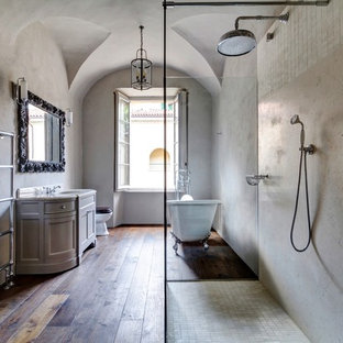 This is an example of a large mediterranean bathroom in London with a walk-in shower, multi-coloured walls, dark hardwood flooring, a built-in sink and an open shower.