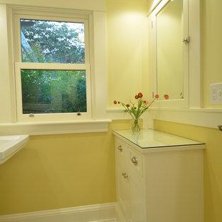 Foto di una piccola stanza da bagno stile americano con ante a filo, ante bianche, piastrelle bianche, piastrelle in ceramica, pareti gialle, pavimento con piastrelle in ceramica, lavabo a colonna e top in vetro