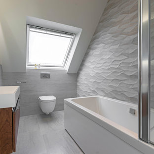 Photo of a medium sized contemporary bathroom in London with flat-panel cabinets, dark wood cabinets, a corner bath, a wall mounted toilet, grey walls, a wall-mounted sink, grey floors and grey tiles.