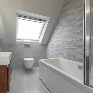 Imagen de cuarto de baño actual, de tamaño medio, con armarios con paneles lisos, puertas de armario de madera en tonos medios, bañera esquinera, sanitario de pared, paredes grises, lavabo suspendido, suelo gris y baldosas y/o azulejos grises