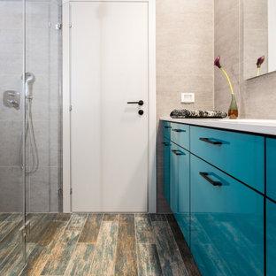Aménagement d'une petit salle d'eau contemporaine avec un placard à porte plane, des portes de placard turquoises, une douche à l'italienne, un WC suspendu, un carrelage gris, des carreaux de porcelaine, un mur gris, un sol en carrelage de porcelaine, un plan vasque, un plan de toilette en surface solide, un sol turquoise, une cabine de douche à porte battante et un plan de toilette vert.