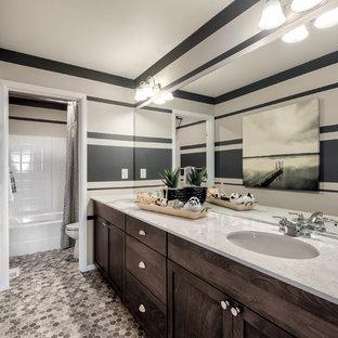 Diseño de cuarto de baño infantil, de estilo americano, grande, con armarios con rebordes decorativos, puertas de armario marrones, combinación de ducha y bañera, sanitario de una pieza, paredes beige, suelo laminado, lavabo bajoencimera, encimera de mármol, suelo multicolor y encimeras blancas