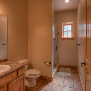 Design ideas for a large mediterranean shower room in Denver with a built-in sink, raised-panel cabinets, medium wood cabinets, laminate worktops, an alcove shower, a two-piece toilet, ceramic tiles, brown walls, ceramic flooring and brown tiles.