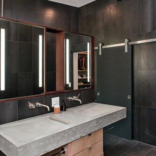 Großes Modernes Badezimmer En Suite mit flächenbündigen Schrankfronten, hellen Holzschränken, offener Dusche, Wandtoilette, schwarzen Fliesen, Porzellanfliesen, schwarzer Wandfarbe, Betonboden, Trogwaschbecken, Beton-Waschbecken/Waschtisch, grauem Boden, offener Dusche und grauer Waschtischplatte in Raleigh