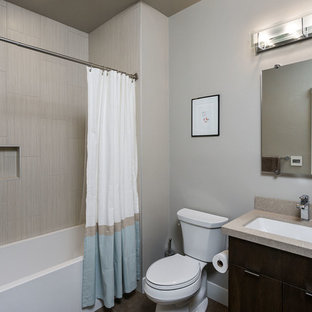 Mid-sized minimalist black tile and porcelain tile porcelain floor bathroom photo in Other with an undermount sink, flat-panel cabinets, dark wood cabinets, quartz countertops, a two-piece toilet and gray walls