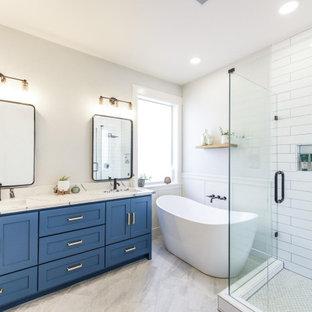 Idéer för ett mellanstort klassiskt vit en-suite badrum, med skåp i shakerstil, blå skåp, ett fristående badkar, en hörndusch, vit kakel, keramikplattor, grå väggar, klinkergolv i porslin, ett undermonterad handfat, bänkskiva i kvarts, grått golv och dusch med gångjärnsdörr
