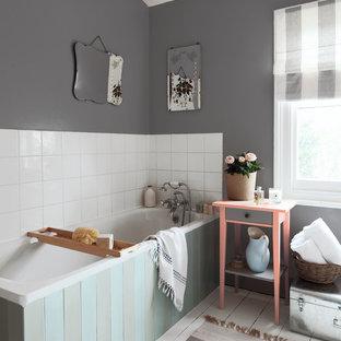 Foto de cuarto de baño contemporáneo con bañera esquinera, paredes grises, suelo de madera pintada y suelo blanco