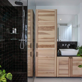 This is an example of a medium sized contemporary family bathroom in London with shaker cabinets, light wood cabinets, a built-in bath, a walk-in shower, a wall mounted toilet, black tiles, terracotta tiles, white walls, porcelain flooring, a console sink, white floors and an open shower.