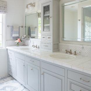 Esempio di una stanza da bagno padronale tradizionale di medie dimensioni con pavimento in marmo, pavimento bianco, doccia alcova, pareti beige, lavabo sottopiano, porta doccia a battente, ante con riquadro incassato, ante grigie, top piastrellato e top bianco
