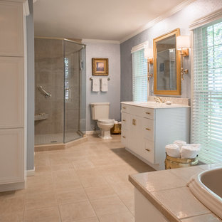 Inspiration for a large timeless master ceramic tile corner shower remodel in Cedar Rapids with blue walls, recessed-panel cabinets, white cabinets, an undermount sink and quartz countertops
