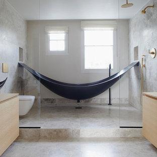 Idéer för mellanstora funkis beige en-suite badrum, med möbel-liknande, skåp i ljust trä, ett fristående badkar, våtrum, en vägghängd toalettstol, grå kakel, kakelplattor, grå väggar, kalkstensgolv, ett fristående handfat, träbänkskiva, grått golv och med dusch som är öppen