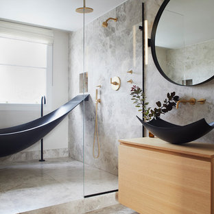 This is an example of a medium sized contemporary bathroom in London with light wood cabinets, a freestanding bath, a wall mounted toilet, grey tiles, limestone tiles, grey walls, limestone flooring, a vessel sink, wooden worktops, grey floors, an open shower, beige worktops and flat-panel cabinets.