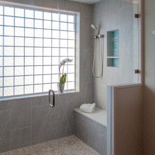 Foto di una grande stanza da bagno padronale minimalista con pareti grigie, pavimento con piastrelle di ciottoli, lavabo sottopiano, ante lisce, ante in legno bruno, top in quarzo composito, doccia doppia, WC monopezzo, piastrelle blu, piastrelle di vetro, pavimento grigio e porta doccia a battente