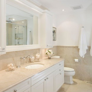 Design ideas for a mid-sized traditional 3/4 bathroom in Ottawa with an undermount sink, recessed-panel cabinets, white cabinets, beige tile, a one-piece toilet, ceramic tile, white walls, beige floor and beige benchtops.