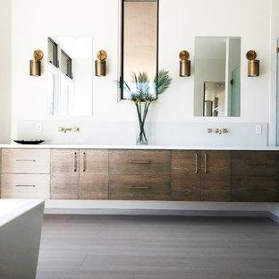 Großes Modernes Badezimmer En Suite mit flächenbündigen Schrankfronten, hellbraunen Holzschränken, freistehender Badewanne, bodengleicher Dusche, Toilette mit Aufsatzspülkasten, weißer Wandfarbe, Porzellan-Bodenfliesen, Unterbauwaschbecken, Quarzwerkstein-Waschtisch, weißem Boden, Falttür-Duschabtrennung und weißer Waschtischplatte in Santa Barbara