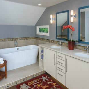 Immagine di una stanza da bagno padronale tradizionale di medie dimensioni con ante lisce, ante bianche, vasca freestanding, WC monopezzo, piastrelle beige, piastrelle di vetro, pareti blu, pavimento in sughero, lavabo sottopiano e top in quarzo composito