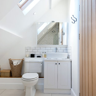 Rural bathroom in London with a vessel sink, white cabinets, a two-piece