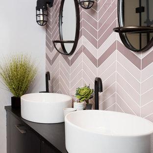Ejemplo de cuarto de baño contemporáneo con lavabo sobreencimera, armarios con paneles lisos, puertas de armario negras, baldosas y/o azulejos rosa y encimeras negras