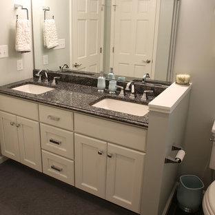 Ejemplo de cuarto de baño de estilo americano con armarios con paneles lisos, puertas de armario blancas, sanitario de dos piezas, baldosas y/o azulejos negros, baldosas y/o azulejos de terracota, suelo de pizarra, lavabo suspendido y encimera de granito
