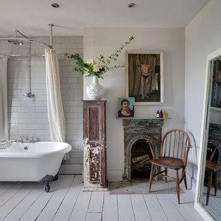 Foto de cuarto de baño romántico con bañera con patas, combinación de ducha y bañera, baldosas y/o azulejos blancos, baldosas y/o azulejos de cemento, paredes blancas y suelo de madera pintada