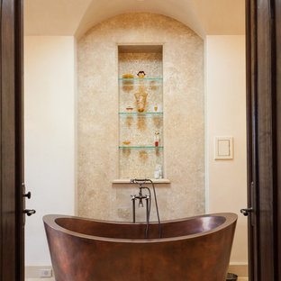 Inspiration for a mediterranean bathroom in Orange County with a freestanding tub, beige tile and beige walls.