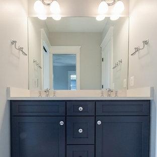 Diseño de cuarto de baño infantil, de estilo de casa de campo, con armarios estilo shaker, puertas de armario azules, encimeras blancas, bañera empotrada, combinación de ducha y bañera, paredes grises, lavabo bajoencimera, suelo multicolor y ducha con cortina