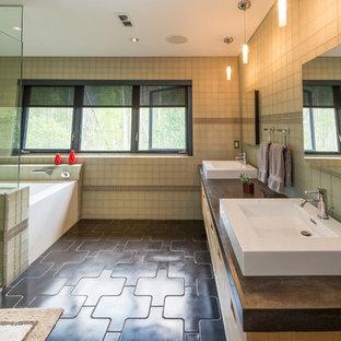 Idee per una grande stanza da bagno padronale minimalista con lavabo a bacinella, top in cemento, ante lisce, ante in legno chiaro, vasca ad alcova, doccia ad angolo, piastrelle beige, piastrelle di vetro, pavimento in cemento, pavimento nero e porta doccia a battente