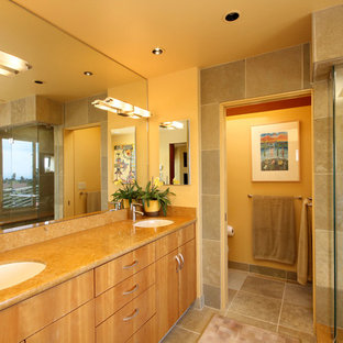 Example of a large transitional master beige tile and ceramic tile ceramic floor and beige floor alcove shower design in San Francisco with an undermount sink, flat-panel cabinets, light wood cabinets, yellow walls and a hinged shower door