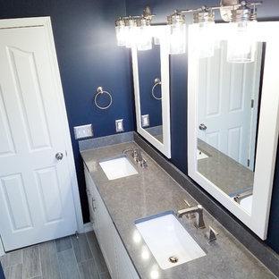 Diseño de cuarto de baño infantil, tradicional renovado, pequeño, con armarios estilo shaker, puertas de armario blancas, bañera empotrada, sanitario de dos piezas, baldosas y/o azulejos blancos, paredes azules, suelo de baldosas de cerámica, lavabo bajoencimera, encimera de cuarzo compacto y suelo gris