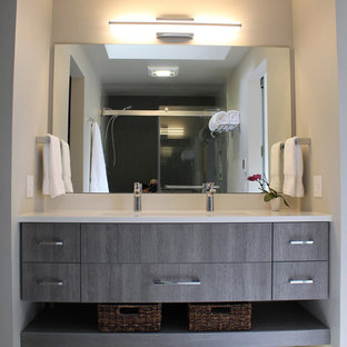 Inspiration for a small modern master gray tile and ceramic tile cement tile floor and gray floor bathroom remodel in Seattle with flat-panel cabinets, gray cabinets, a one-piece toilet, gray walls, a trough sink, quartz countertops and white countertops