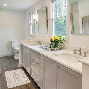 Klassisches Badezimmer En Suite mit Schrankfronten mit vertiefter Füllung, grauen Schränken, Wandtoilette mit Spülkasten, weißer Wandfarbe, braunem Holzboden, Unterbauwaschbecken, braunem Boden und weißer Waschtischplatte in Boston