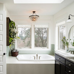 Design ideas for a large transitional master bathroom in Portland with a drop-in sink, a drop-in tub, green tile, white walls, shaker cabinets, black cabinets, glass tile, porcelain floors and granite benchtops.