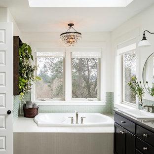 Idee per una grande stanza da bagno padronale tradizionale con lavabo da incasso, vasca da incasso, piastrelle verdi, pareti bianche, ante in stile shaker, ante nere, piastrelle di vetro, pavimento in gres porcellanato e top in granito