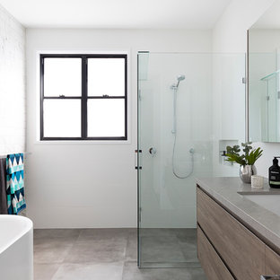 Mid-sized contemporary 3/4 bathroom in Brisbane with medium wood cabinets, a corner tub, a corner shower, a one-piece toilet, white tile, ceramic tile, white walls, cement tiles, an undermount sink, engineered quartz benchtops, grey floor, a hinged shower door, grey benchtops and flat-panel cabinets.