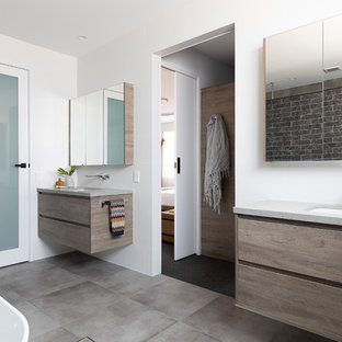 Large contemporary master bathroom in Brisbane with flat-panel cabinets, medium wood cabinets, a freestanding tub, a double shower, a one-piece toilet, white tile, ceramic tile, white walls, ceramic floors, an undermount sink, engineered quartz benchtops, grey floor, a sliding shower screen and grey benchtops.