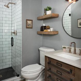 Bild på ett mellanstort industriellt grå grått badrum med dusch, med skåp i mellenmörkt trä, en toalettstol med separat cisternkåpa, vit kakel, keramikplattor, blå väggar, klinkergolv i porslin, ett undermonterad handfat, bänkskiva i kvarts, svart golv och dusch med gångjärnsdörr