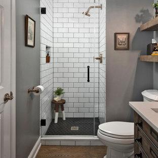 Exempel på ett mellanstort klassiskt grå grått badrum med dusch, med en toalettstol med separat cisternkåpa, vit kakel, keramikplattor, klinkergolv i porslin, ett undermonterad handfat, bänkskiva i kvarts, dusch med gångjärnsdörr, skåp i mörkt trä, en dusch i en alkov, grå väggar och brunt golv