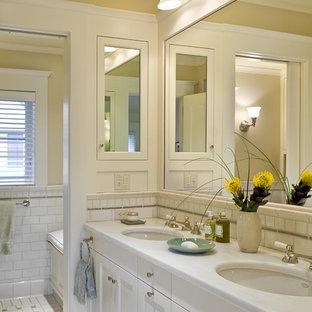 Ejemplo de cuarto de baño clásico con lavabo bajoencimera, armarios con paneles empotrados, puertas de armario blancas, baldosas y/o azulejos blancos y baldosas y/o azulejos de cemento