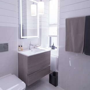 Inspiration for a small modern master white tile and porcelain tile porcelain tile and white floor alcove shower remodel in New York with flat-panel cabinets, brown cabinets, a wall-mount toilet, white walls, an integrated sink and a hinged shower door