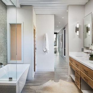 Modelo de cuarto de baño principal, urbano, con armarios con paneles lisos, puertas de armario de madera oscura, bañera exenta, ducha empotrada, baldosas y/o azulejos grises, baldosas y/o azulejos en mosaico, paredes blancas, lavabo bajoencimera, suelo beige, ducha con puerta con bisagras y encimeras blancas