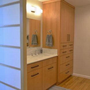 Ejemplo de cuarto de baño principal, de estilo zen, de tamaño medio, sin sin inodoro, con armarios con paneles lisos, puertas de armario de madera oscura, sanitario de una pieza, paredes beige, suelo de madera en tonos medios, lavabo integrado y encimera de acrílico