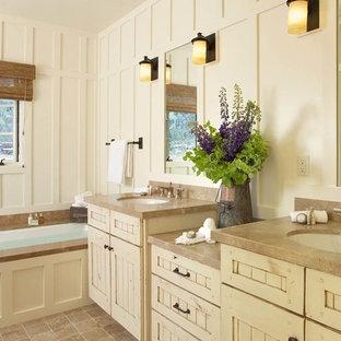 Diseño de cuarto de baño rural, de tamaño medio, con armarios estilo shaker, puertas de armario con efecto envejecido, bañera empotrada, paredes blancas, lavabo bajoencimera y suelo marrón