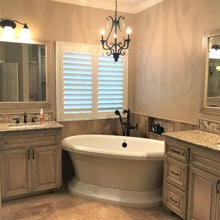Cette image montre une salle de bain principale traditionnelle avec un placard avec porte à panneau surélevé, des portes de placard en bois vieilli, une baignoire indépendante, une douche d'angle, un carrelage beige, du carrelage en travertin, un mur beige, un sol en travertin, un lavabo encastré, un plan de toilette en granite, un sol beige, une cabine de douche à porte battante et un plan de toilette jaune.