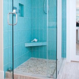 Imagen de cuarto de baño principal, bohemio, de tamaño medio, con armarios con paneles lisos, puertas de armario blancas, bañera exenta, ducha esquinera, sanitario de una pieza, baldosas y/o azulejos azules, baldosas y/o azulejos de vidrio, paredes blancas, suelo de baldosas de cerámica, encimera de vidrio y lavabo sobreencimera