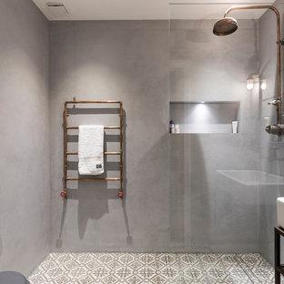Immagine di una stanza da bagno per bambini industriale di medie dimensioni con doccia aperta, piastrelle di vetro, pareti grigie, pavimento in cementine e lavabo a bacinella
