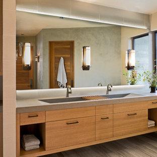 Bild på ett mellanstort rustikt badrum, med travertin golv, bänkskiva i betong, släta luckor, skåp i mellenmörkt trä, ett avlångt handfat och grått golv