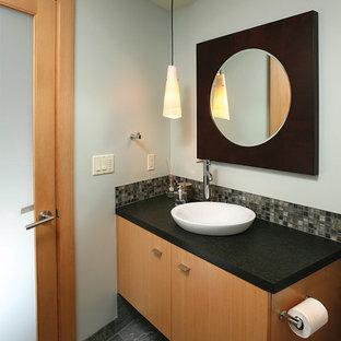 Immagine di una stanza da bagno con doccia contemporanea di medie dimensioni con lavabo a bacinella, ante lisce, ante in legno scuro, top in granito, piastrelle nere, piastrelle in pietra e pareti blu